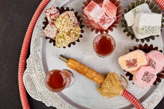 Set of various turkish delight in bowl on metal tray near hookah tube Premium Photo