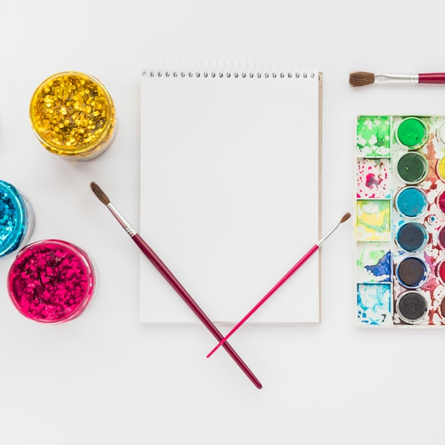 Set of water color and glitter color with spiral notepad isolated on white backdrop Free Photo