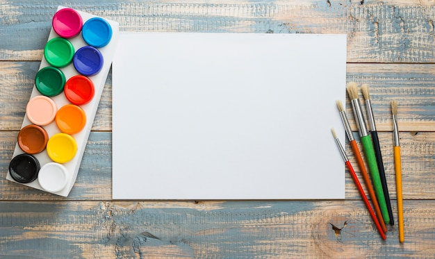 Set of water colors and paint brush with empty blank white paper over old wooden table Free Photo