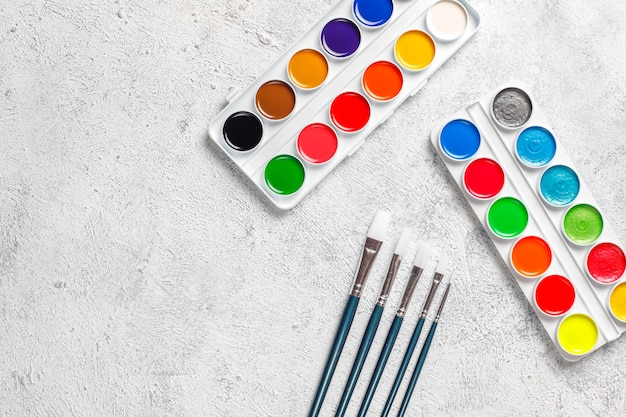 Set of watercolor paints and paintbrushes for painting. Free Photo
