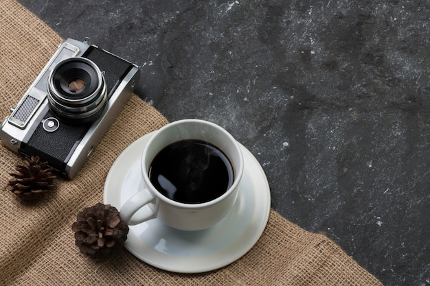 Set white cup coffee and old camera , pine dry on burlap in black stone Premium Photo