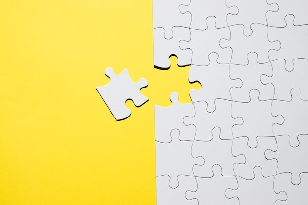 Set of white jigsaw puzzle pieces over yellow backdrop Free Photo