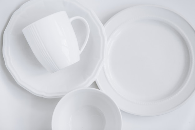 Set of white utensils from three different plates and a cup in a plate Free Photo
