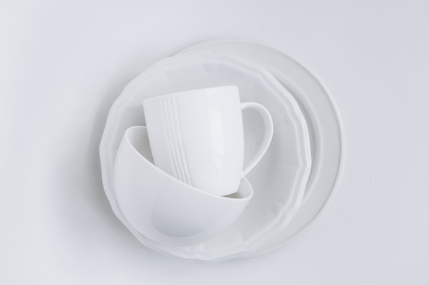 Set of white utensils in a stack of three different plates and a cup Free Photo