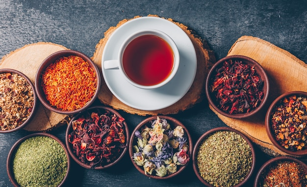 Set di tronchi di legno e una tazza di tè ed erbe di tè in una ciotole su uno sfondo scuro con texture. disteso. Foto Gratuite
