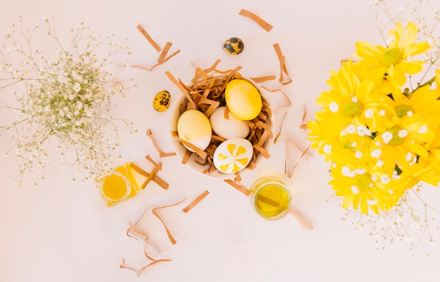 Set Of Yellow Easter Eggs In Bowl Between Fresh Flowers And Cans Of