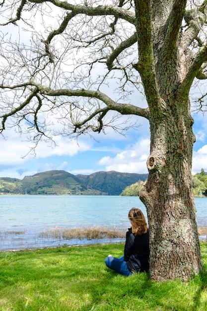 Девушка рассматривая озеро в горы, азорские островы sete cidades, португалия. Premium Фотографии