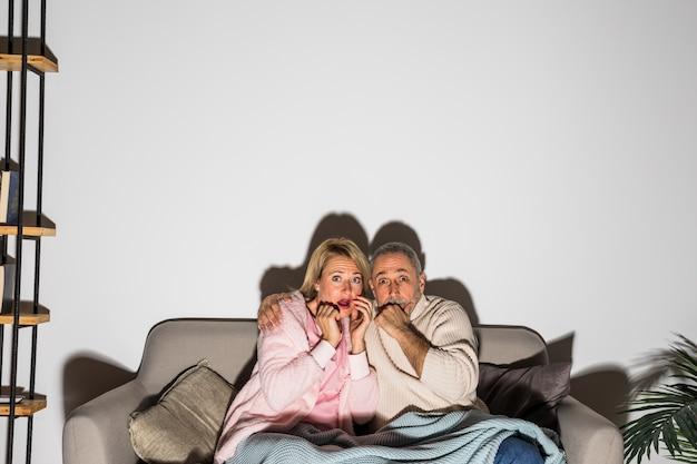 シニア怖い人女性とハグし、setteeでテレビを見ています。 無料写真