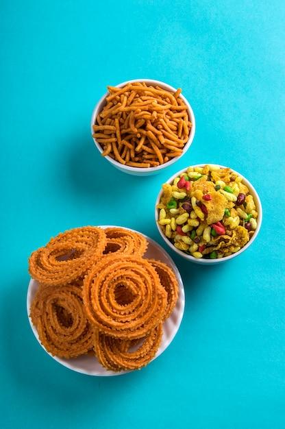 インドのスナック:チャクリ、チャカリまたはムルックとブザン(グラム小麦粉)sevとchivadaまたは青の背景にchiwada。ディワリフード Premium写真