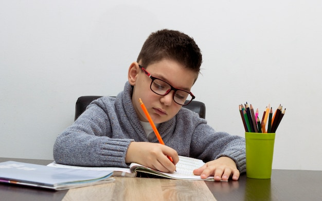 Seven years old child writing at home Boy studying at table Kid