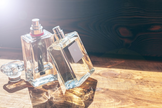 Several bottles with perfume in rays of sunshine on wooden table Premium Photo