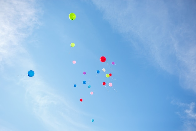 Several coloured air balloons are flying into the blue sky Premium Photo