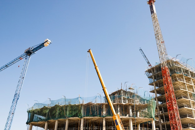 Several cranes in front of construction building against blue sky Free Photo