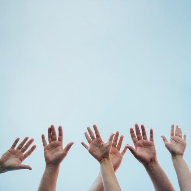 いくつかの手を空中で上げる Premium写真