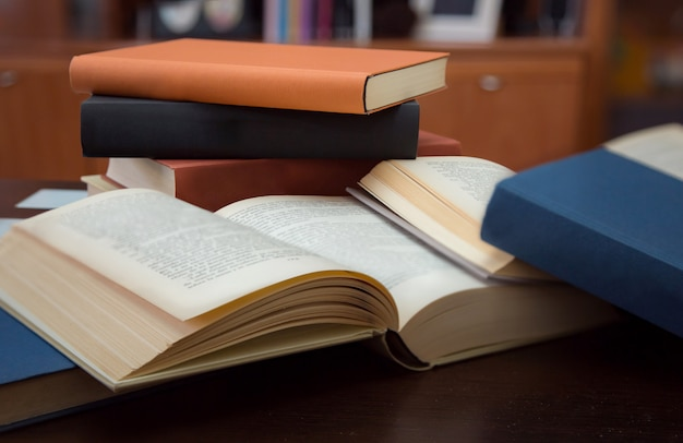 Several open and closed books on wooden table Premium Photo