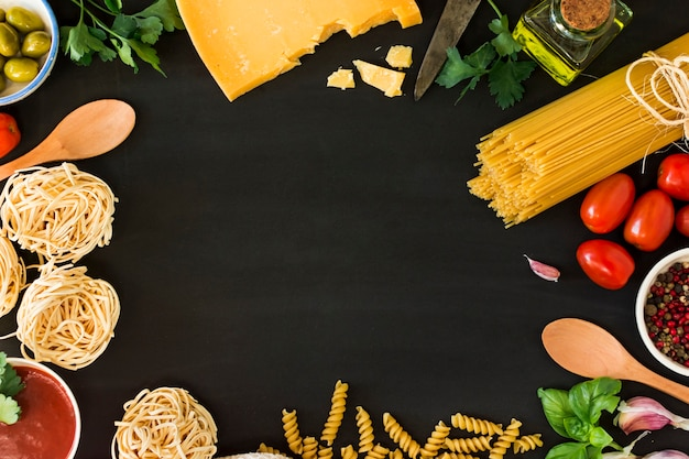 Several types of dry pasta with vegetables and herbs on black background Free Photo