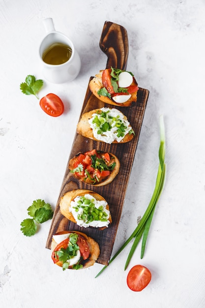 Several types of italian bruschetta with tomatoes, mozzarella and herbs on a wooden board Premium Photo