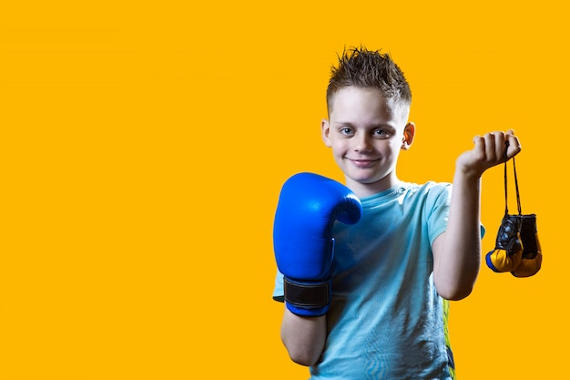 Severe boy in blue boxing gloves on bright yellow Premium Photo