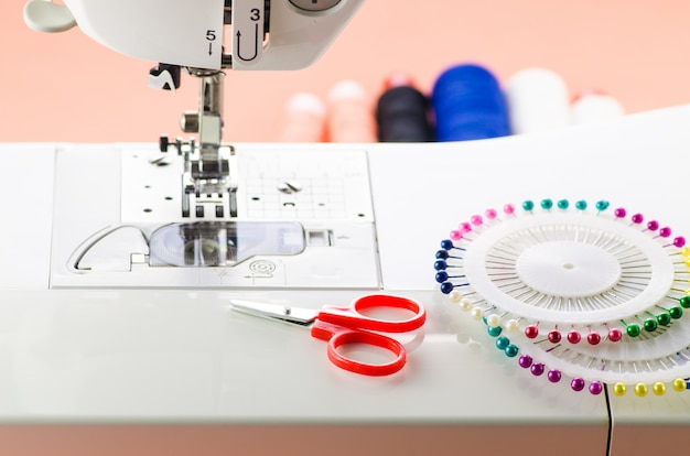 Sewing accessories are on a white sewing machine: scissors and english needles Premium Photo