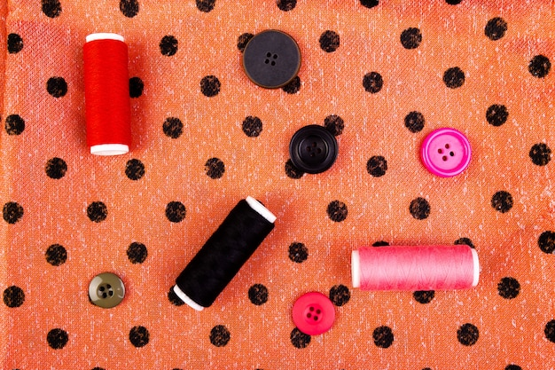 Sewing buttons, spools of thread and cloth on wooden table Premium Photo