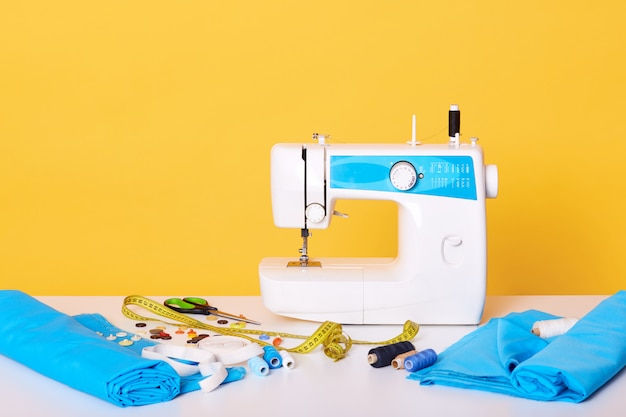 Швейное оборудование, швейная машина, метчик, ножницы, кусочки ткани, иглы, нить, изолированных на желтом. разные инструменты в швейной мастерской, Бесплатные Фотографии