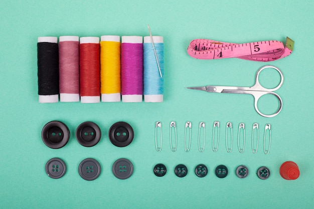 Sewing kit accessories.set tools for tailoring and colorful threads,needles,pins,scissors on green background top view. Premium Photo
