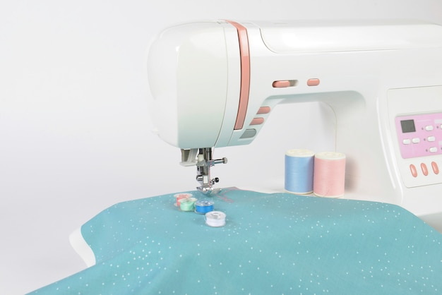 Sewing machine and colorful thread rolls, scissors, fabric and accessories for sewing. Premium Photo