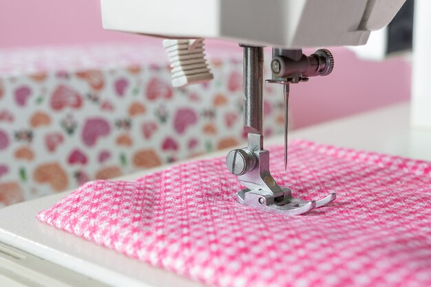 Sewing machine, pink fabric needle close-up with selective focus on a light background with copy space Premium Photo