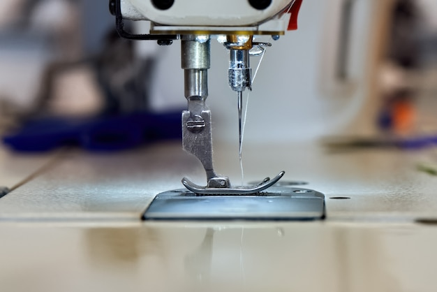 Sewing machine and white thread close up Free Photo