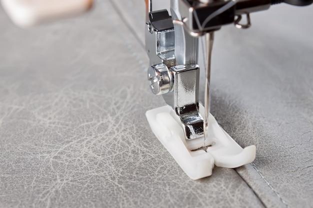 Швейная машина со специальной лапкой выполняет шов на серой коже. процесс шитья крупным планом Premium Фотографии