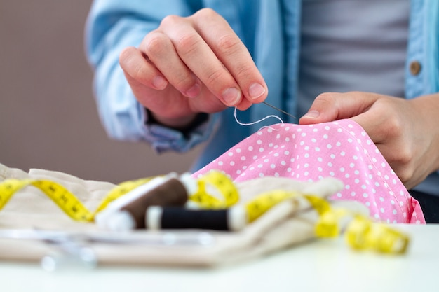 Sewing process. housewife sews at home using needle and various sewing accessories Premium Photo