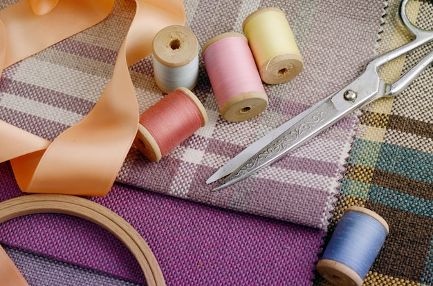 Sewing supplies, needles, vintage scissors on the colorful gunny textile Premium Photo