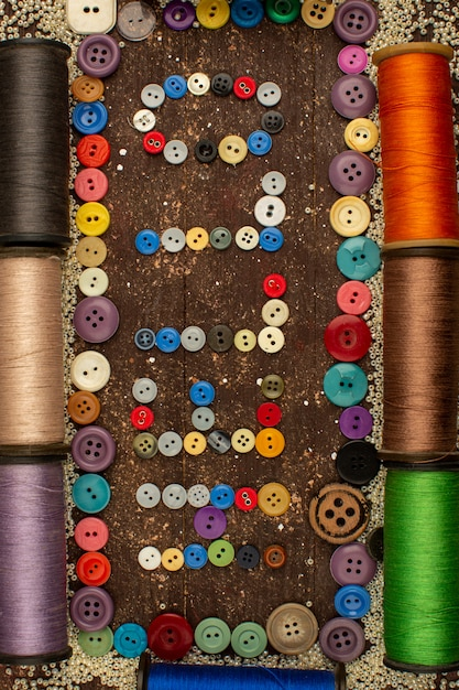 Швейные нитки вместе с пластиковыми красочными пуговицами, образующими привет слово на коричневом деревенском столе Бесплатные Фотографии