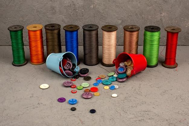 Швейные нитки разноцветные вместе с разноцветными пластиковыми винтажными пуговицами на сером Бесплатные Фотографии