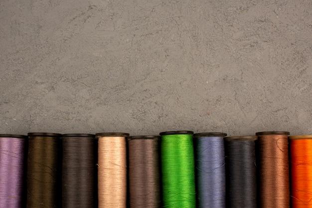 Швейные нитки разноцветные разные на сером фоне Бесплатные Фотографии