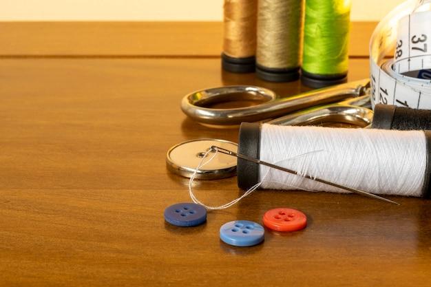 縫製トリム。糸、針、ボタン、はさみ、巻尺のスプール。 Premium写真
