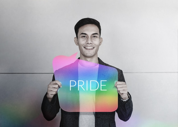 Sexual minority and lgbt concept. happy young gay smiling and show pride text on rainbow card Premium Photo