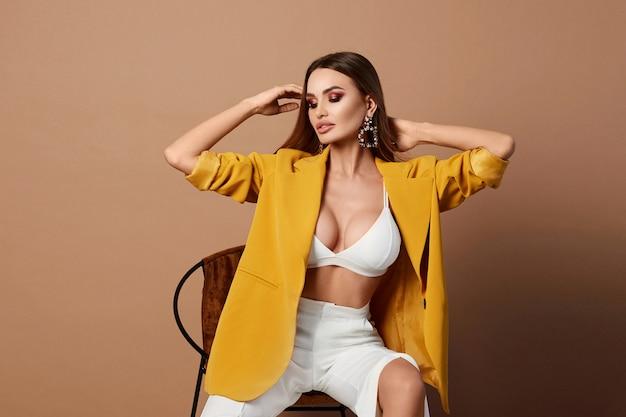 Sexy adult woman in the stylish yellow blazer posing Premium Photo