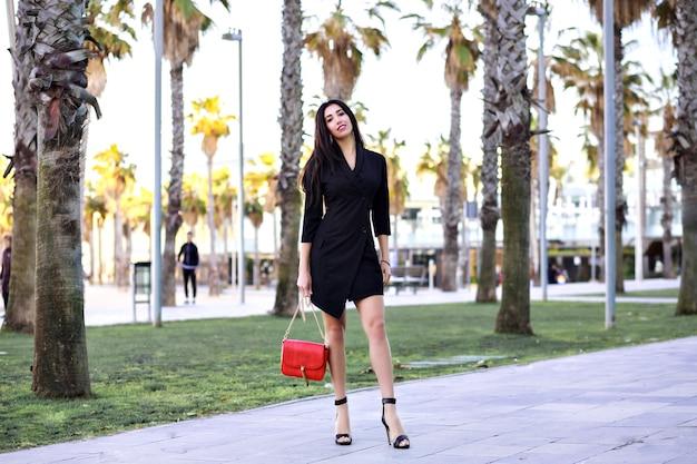 Attraente donna sicura di sé sexy che cammina per strada con palme, vestito nero minimalista da donna di affari moderna, viaggiando in spagna. Foto Gratuite