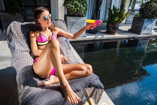 プールで遊ぶプラスチック製の水鉄砲を楽しんでセクシーな美しい女性 無料写真