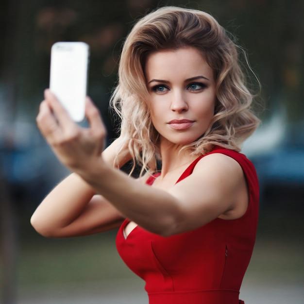 Сексуальная красивая молодая блондинка модель красное платье делает себя в природе размытым Premium Фотографии
