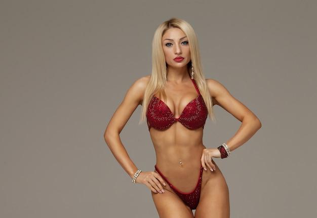 Яркая блондинка с красным цветком в волосах без трусиков у бассейна