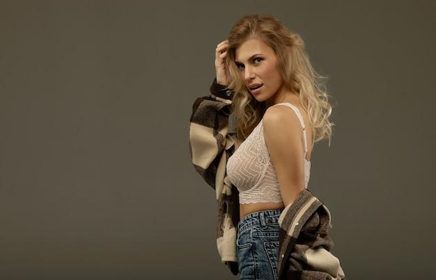전체 입술 속옷과 청바지에 포즈와 섹시 한 금발 소녀. 프리미엄 사진
