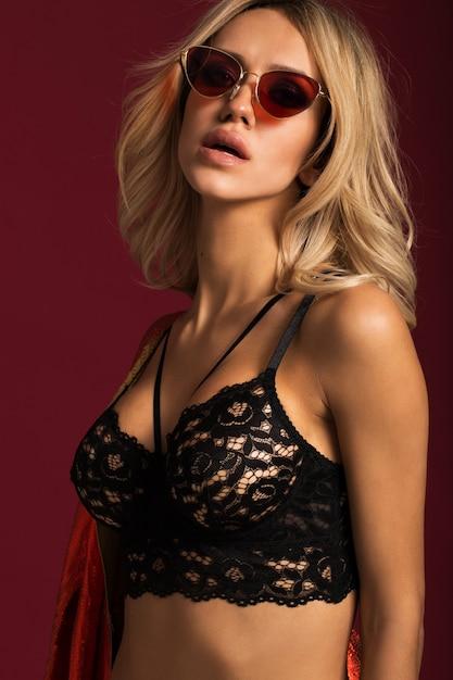 빨간 벽에 안경과 검은 속옷에 섹시한 금발 프리미엄 사진
