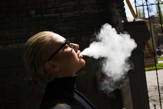 Sexy blonde smokes and releases smoke Premium Photo