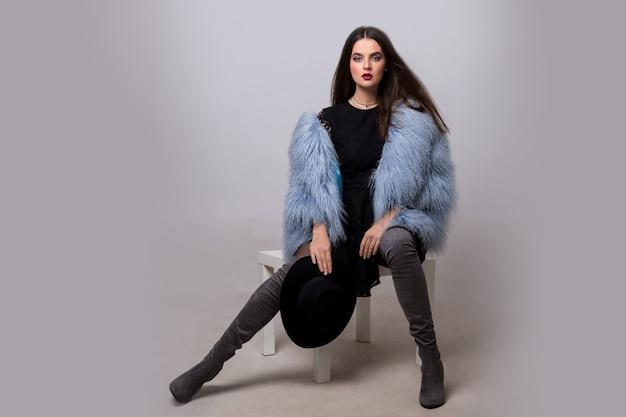 トレンディな青い毛皮のジャケットと灰色の壁にポーズをとるベルベットの太いハイブーツのセクシーなブルネットの女性。 無料写真