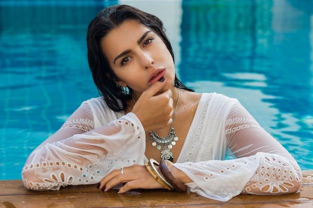 スタイリッシュな夏服でプールの近くに座っているセクシーなブルネットの女性。熱帯の休暇。 無料写真