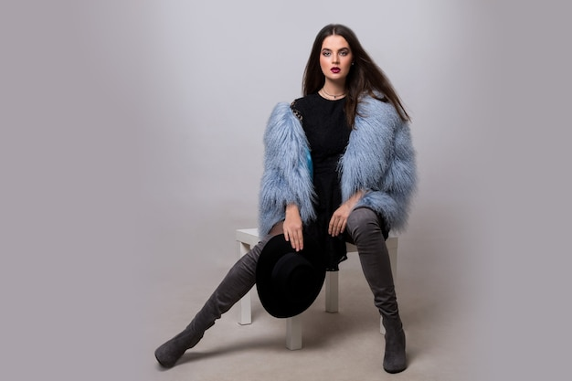 Sexy brunette woman in trendy blue fur jacket and velvet thight high boots posing on grey wall.