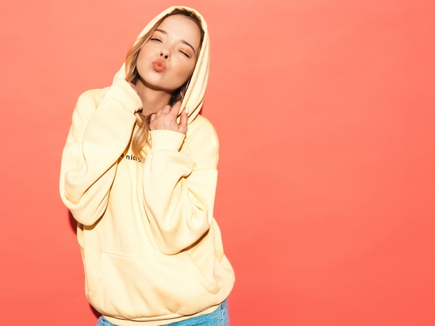 Sexy carefree woman posing near blue wall. positive model having fun in hood.makes duck face Free Photo