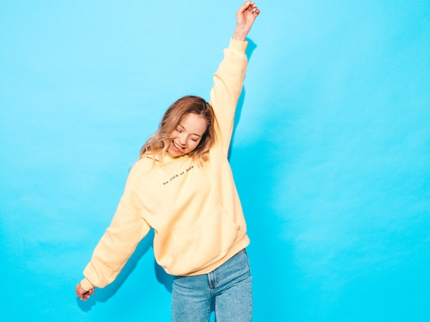 Sexy carefree woman posing near blue wall. positive model having fun.raising her hands and shows tongue Free Photo
